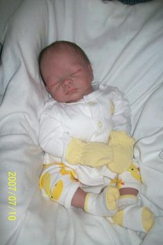 reborn baby doll wearing yellow mittens