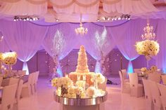 Glowing white wedding tent reception by Mindy Weiss / white floral cake