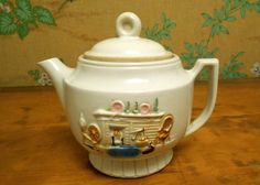Porcelier Vitreous Glass Teapot. This beautiful vintage teapot features an old country hearth design on the front.