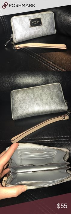 Michael Kors wristlet Michael Kors wristlet in silver with tan wrist strap. Will fit an iPhone 5 or similar sized phone. There are a few scratches on the front face plate and 2 frayed threads on the back (see photos).  The inside and wrist strap show no signs of wear.  I used this for a short while as a wallet and carried it inside my bag so it still looks really clean all around. Michael Kors Bags Clutches & Wristlets
