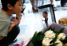 A boy looks at a figure of Steve Jobs next to flowers laid in his tribute at an Apple store in Hong Kong, China.