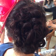 Looped updo for a wedding with fascinator
