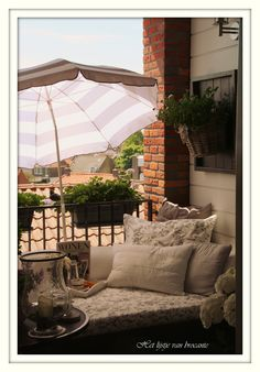 This balcony has it all:  Comfy seating thanks to lots of pillows and a cushion, plus an adjustable umbrella so you can keep yourself protected from the sun as it moves across the sky.  You'll never go back inside your apartment again!