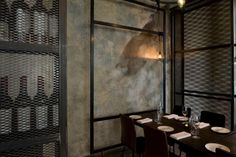 The metal mesh panels and plaster walls create texture within a neutral color palette.