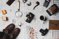 A flatlay of a magnifying glass, a cup of coffee, cameras, photos and various travel items on a map