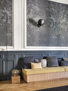 Just opposite, Hermand installed a built-in banquette with drawers for storage. The sconces are Cobra Wall Lamps by Greta Grossman for Gubi. Toward the left of the frame, a door is cut fully into the wall with wainscot, molding, and wallpaper intact.