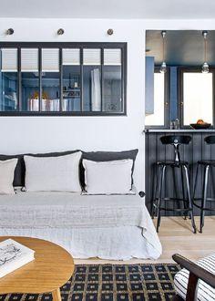 <p>Dans ce petit appartement, la cuisine communique avec le salon par une double solution ingénieuse. Une mini verrière se place au-dessus de la banquette du coin salon. Dans son...