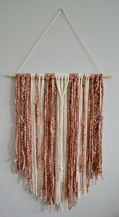 Wall Hanging in blush pink, rust and cream yarn. Add the perfect amount of boho chic decor with one of these yarn wall hangings! Choose in the drop down menu whether you want 12 width or 24 width. Length measurements are approximate and can vary between 32 and 36. The picture you see will not be the item you will receive. Due to the fact that each item is handcrafted, products can vary slightly. We love custom orders! Message us your thoughts and colors youd like to have and we will make ...
