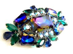 A Verified Vintage Juliana Watermelon Heliotrope Brooch With Rainbow Flashes Among Blue And Green Rhinestones Accented By Aurora Borealis. In Exquisite High Fashion style, this DeLizza and Elster Brooch features Juliana's Watermelon Heliotrope stones, named for the fantastic gemstone known as Watermelon Tourmaline by JewelryQuestDesign