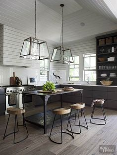 Shiplap paneling painted pale gray runs the length of this minimalist kitchen. The absence of upper cabinets showcases high ceilings and allows for unobstructed window views. Oversize light fixtures frame a rustic island accented with uncomplicated metal-base bar stools.