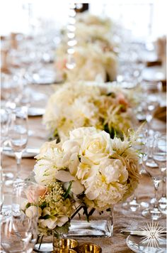 Wedding flowers are beautiful here on the table for this gorgeous runner for the reception