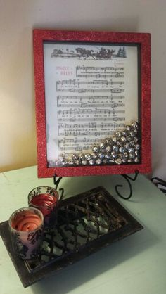 Red glittered shadow box with jingle bells and old Jingle Bell sheet music by CN