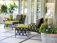 The black lounge chairs on this cozy patio mimic the diamond pattern of the black and white flooring. Chartreuse cushions add a fun punch of color, while planted flowers add a romantic touch.