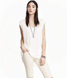 Long, V-neck, straight-cut tank top in jersey with a seam at back. Rounded hem, longer at back.