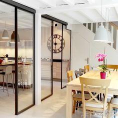 Cuisine ouverte sur la salle à manger grâce à de grandes verrières tout hauteur.