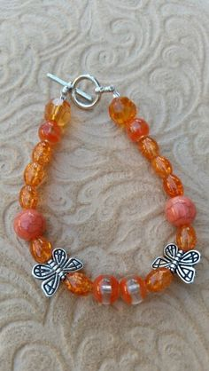 Orange beads with butterfly charm beads
