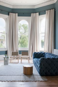 A Paola Navone Chester Moon Sofa in blue anchors the living room. Off-white linen curtains add privacy to the street-facing front room. Source by remodelista Rideaux Du Bow Window, Bay Window Design, Living Room Designs, Living Room Decor, Living Spaces, Hecker Guthrie, White Linen Curtains, Neutral Curtains, Blue Drapes