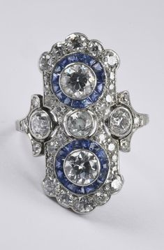An Art Deco platinum, diamond and sapphire ring, 1920s/30s. The flat bezel geometrically set with old- and transition-cut diamonds. The two large transition-cut diamonds surrounded by calibrated natural sapphires.