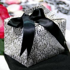 100 Tote Favor Boxes - Black/White Flocking   This shinning favor box is made of embossed cardboard.  Its elegant color and classic design allows you to present your charming favors with grace. Each side is tapered for an exquisite and decorative appearance. This box is the ideal size for holding slightly larger favors, like candle, or even a piece of cake.  Boxes arrive flat-packed, and can be assembled in a snap.
