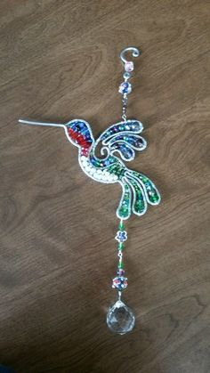Wire wrapped beaded hummingbird sun catcher with crystals.