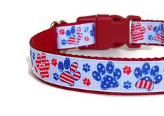 Do you want to show your patriotism? Then this collar is for you! This dog collar is made from red nylon webbing layered with durable grosgrain ribbon with a red, white, and blue paw print pattern. Available in adjustable sizes ranging from 10 to 24, it fits a wide size range of dogs. Perfect for a All-American dog!   TYPES OF COLLARS:  -BUCKLE- An adjustable collar with a plastic or metal side-release buckle. -MARTINGALE - Martingale collars do not have a buckle or D-ring for tags. They…