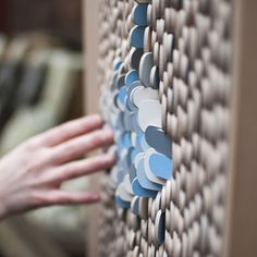 the small wooden scales on this cabinet by swedish designer jenny ekdahl can be flipped to create patterns based on water and waves