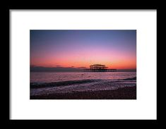 Brighton Pier At Sunset Framed Print by Marius Comanescu. All framed prints are professionally printed, framed, assembled, and shipped within 3 - 4 business days and delivered ready-to-hang on your wall. Choose from multiple print sizes and hundreds of frame and mat options.