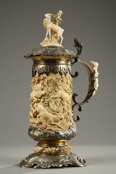 Silver and ivory beer stein intricately sculpted with a hunting scene featuring hunters, deer, bucks, dogs, and topped with a billy goat. The scrolling handle is decorated with a woman wearing a fl...