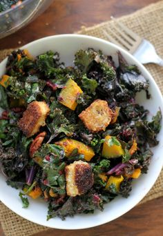This kale salad makes for the perfect Thanksgiving side dish with its mix-ins of roasted squash, cumin-spiced pecans, brie croutons, and cranberry vinaigrette.