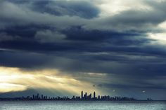 From Coolangatta #GoldCoast: To the north, rain clouds marched across the skies, punctuated by shafts of light drawing attention to the unmistakable silhouette of Surfers Paradise.