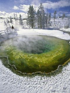 The vivid hues of Yellowstone National Park's steaming Morning Glory Pool stand out in stark contrast from its snow-covered surroundings. by Michael Melford