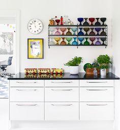 I två nyproducerade stringhyllor i köket står Evas sköna installation av Marimekkos färgglada glasskålar för Iitalla.
