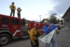 Snohomish County fire crews in the thick of fight in Okanogan. Omak resident Pat Charles, right, shows Lake Roesiger firefighter Scott Anderson a map of the back roads in the hills above his house as Everett fire crew members Matt Park, left (on the truck) and Captain Brent Stainer keep a lookout on an encroaching fire Friday evening.