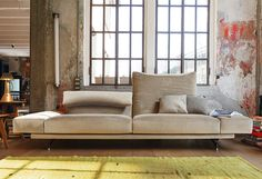 550 Altopiano is a customizable sofa and is available in three variants: with classic upholstered armrests, wing-like adjustable upholstered armrests or also with a Canaletto walnut wood small container in place of the armrest which can also be equipped with a designer lamp. It is available as a single sofa or completed with a comfortable chaise-longue. design: Gianluigi Landoni
