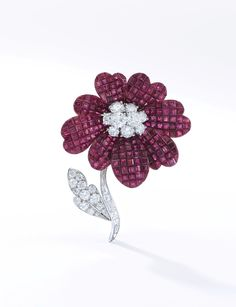 Ruby and diamond brooch, Van Cleef & Arpels Of floral design, the petals set with calibré-cut rubies en serti mystérieux, the pistil embellished with brilliant-cut diamonds, the detachable stem and leaf set with brilliant-cut and baguette diamonds, signed Van Cleef Arpels, numbered, French assay and maker's marks, pouch stamped Van Cleef & Arpels.