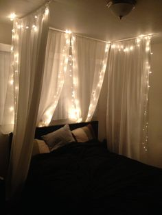"DIY bed canopy under $50! Joann's 84"" home sheer fabric, painted wooden dowels, white ceiling hooks, Christmas lights, and a stapler. No sew! Less than an hour. #christmaslightsceiling"