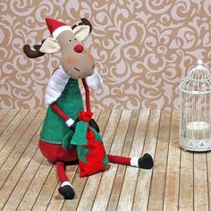 Renifer w czapce św. Mikołaja i workiem z prezentami.