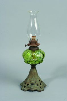 Kerosene lamp with a pierced metal base and a green glass font…