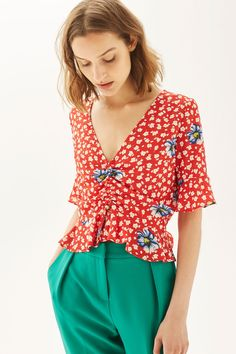 Ruched tops are having a moment. This cute short sleeve top in all over red and blue floral print is our go-to piece this Spring. Pair with colourful trousers or jeans to elevate your look.