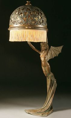 AN ART NOUVEAU BRONZED METAL FIGURAL TABLE LAMP probably Austrian circa 1900 of a winged nymph, after a model by R. Elias. With pierced scrolling filigree bronze shade.