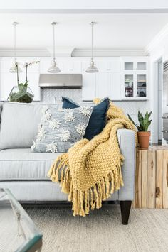 Love that couch, the yellow blanket and the textured pillows