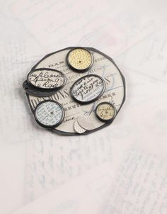 French bills brooch   found ephemera, silver, gold, gold leaf, perspex   by Clare Hillerby @ Contemporary Applied Arts, London