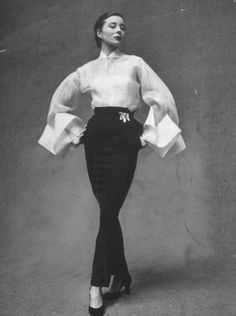 Paris Spring Fashions  Model showing off elegant white organdy shirt featuring huge folded cuffs w. black skirt by Lavin-Castillo.  Location:	Paris, France  Date taken:	February 1951  Photographer:	Gordon Parks
