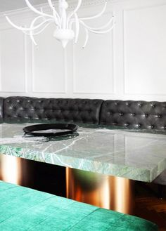 Sleek bright green granite and brass dining table with both green velvet and black leather bench seating.