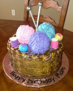 """Yarn Basket Cake - This is a 10"""" round cake frosted in Pastry Pride. The basket weave was airbrushed in brown. The yarn balls are RKT dipped in tinted white chocolate. Once set, I zig zagged chocolate with piping tip 4. The spools of thread and pin cushions are cake balls. The knitting needkes were wood dowels painted in silver air brush pain. Thanks for looking!"""