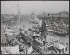 The scene at Woolloomooloo, Australia, 19 Nov. 1945, as the British Pacific Fleet lay in harbour at Sydney following the Japanese surrender. In the distance, the stern of HMS King George V is clearly visible with her unique quadruple turrets, which had four years earlier fired upon the Bismarck. The photograph is believed to have been taken from the Fleet aircraft carrier HMS Indefatigable, whose dual-purpose 4.5 inch guns can be seen elevated just beyond an octuple 2-pdr (1.6″)…