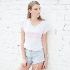 On Wednesdays We Wear Pink Crop top Worn a few times. Great condition.  Brandy Melville super soft cotton. Very light  grey with pink lettering Brandy Melville Tops
