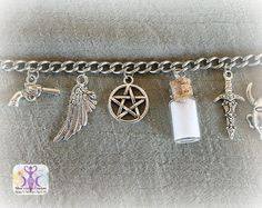 "Join Sam and Dean on their hunting adventures with this ""Supernatural"" inspired charm bracelet from Inked Goddess Creations. Made from stainless steel and pewter, this bracelet includes (from left to"