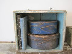 ANTIQUE HANGING BOX IN BLUE PAINT with BLUE PANTRY BOXES & FABRIC COVERED BOOKS.