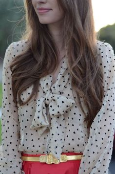 Blouse with heart print and coral skirt with gold belt.